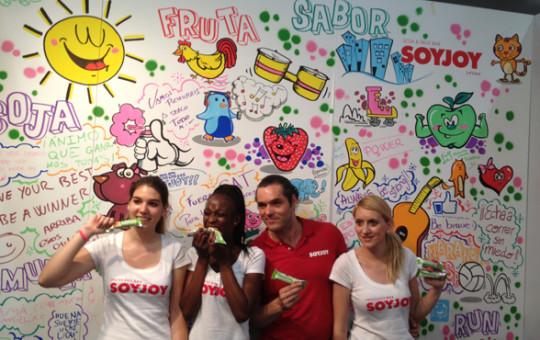 Los azafatos de Soyjoy posando en el stand con el graffiti participativo terminado