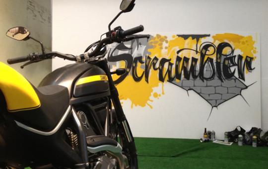 Moto Scrambler de Ducati junto a Graffiti en evento